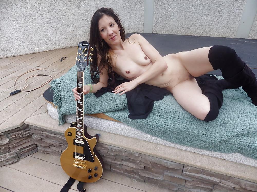 Nude woman playing guitar