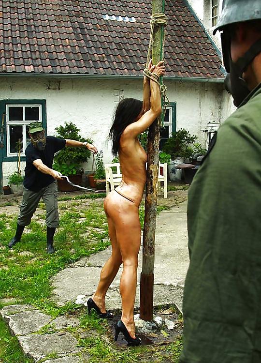 приоткрытого рта девушку привязывают к столбу и накачивают водой минета, которым