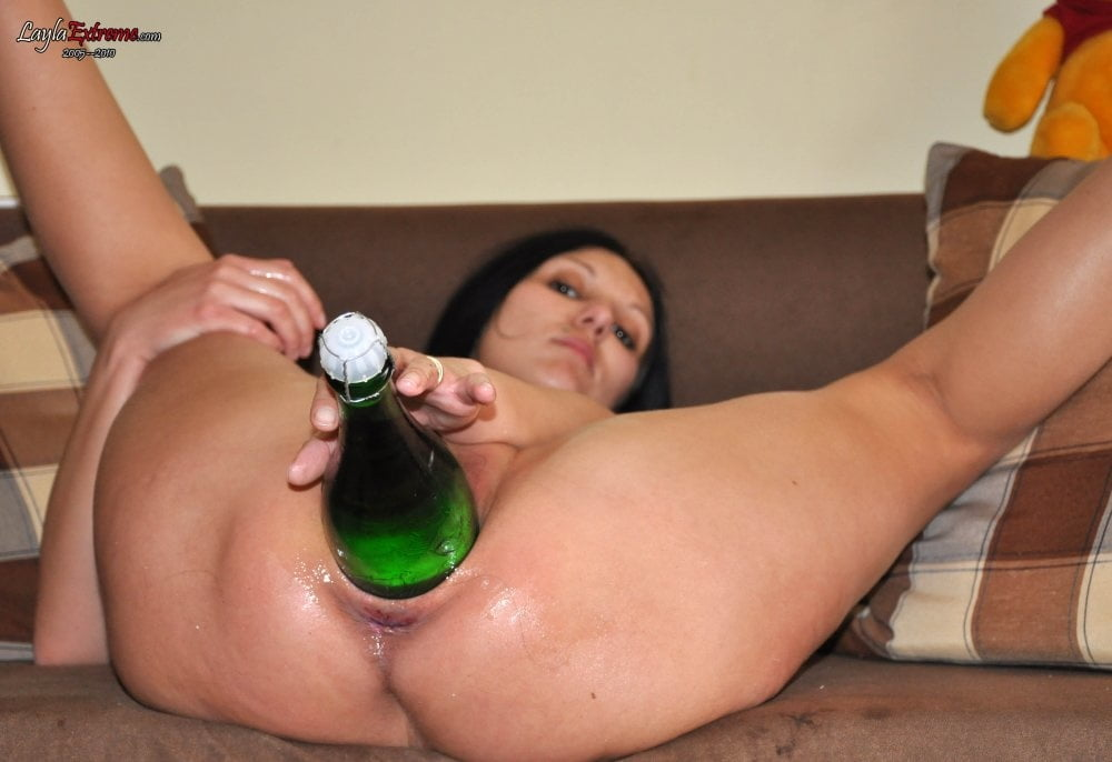 Girl puts a full wine bottle in pussy